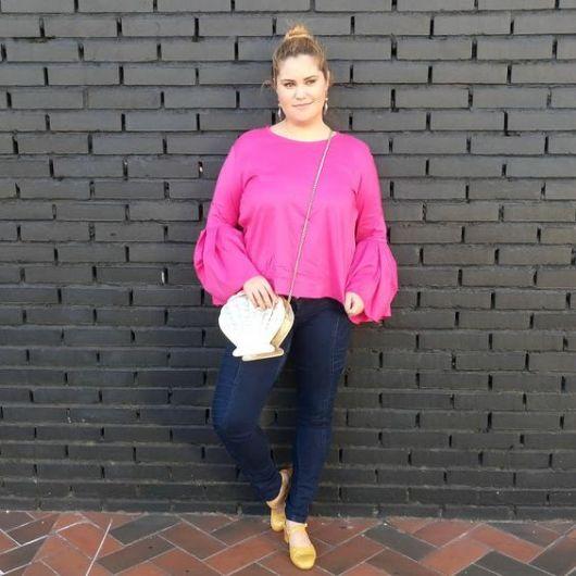 Mulher com blusa com mangas bufantes e bolsa de concha.