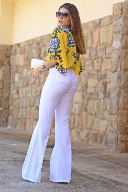 Mulher usando calça branca flare e camisa floral.