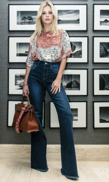 Mulher usando calça flare jeans.
