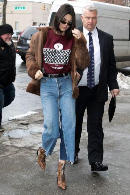 Jendall Jenner com calça flare e camiseta bordo.