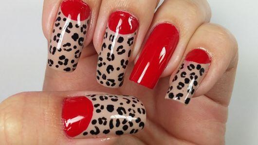 unhas vermelhas decoradas com oncinha.