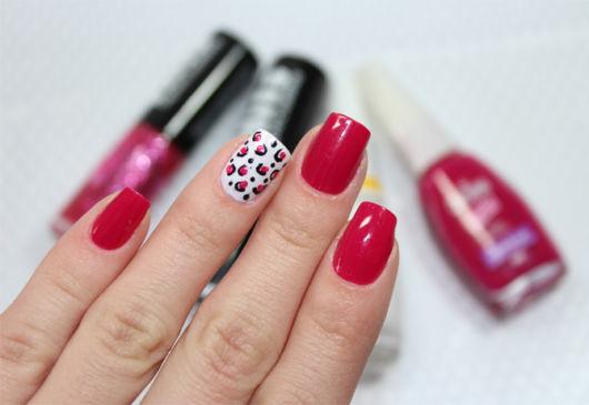 unhas decoradas com esmalte vermelho e um dedo pintado de branco com estampagem de oncinha.