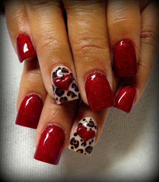 unhas pintadas de vermelho com decoração de oncinha.