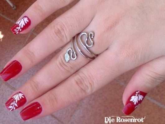 unhas decoradas com esmalte vermelho e flores brancas.