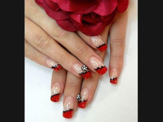 unhas vermelhas decoradas pela metade com esmalte preto.