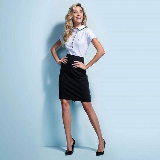 modelo veste camisa polo branca e saia preta e scarpin preto.