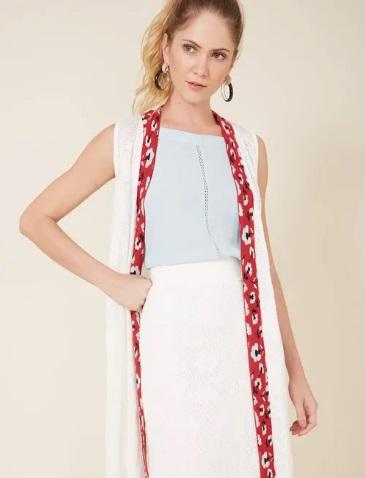 Modelo com colete branco e blusa azul claro.