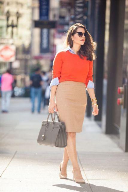 Mulher com saia bege, camisa azul e blusa laranja por cima.