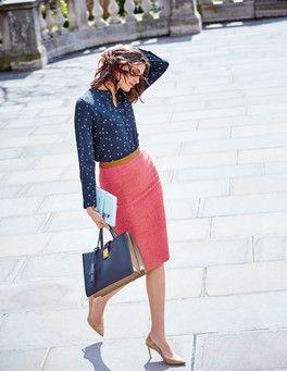 Mulher com saia rosa e camisa azul escura.