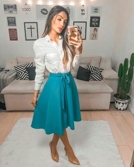 Mulher com saia rodada azul petróleo e camisa branca.