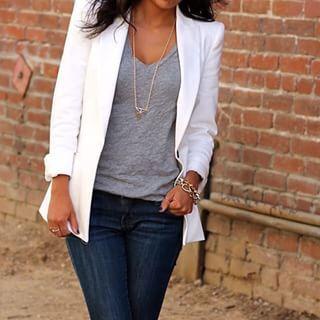 Mulher com calça jeans escura, blusa cinza e blazer branco.