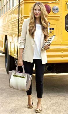 Mulher com alça social sob os tornozelos, blusa branca e casaco nude.