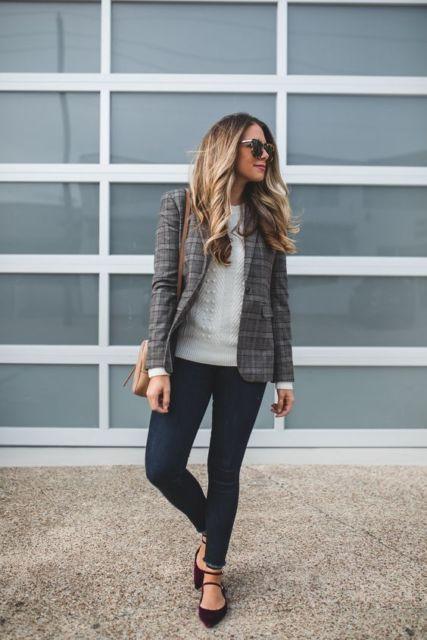 Mulher com calça jeans escura, blusa branca e casaco.