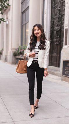 Mulher com calça jeans, blusa listrada e blazer claro.