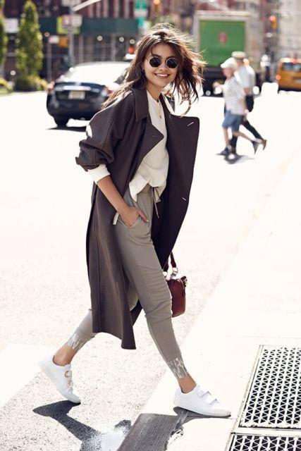Mulher com calça neutra, sobretudo e tênis branco.