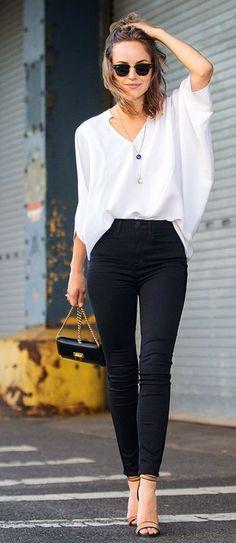 Mulher com calça preta social e blusa branca com manga morcego.