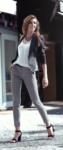 Mulher com calça social, blusa branca e blazer preto.