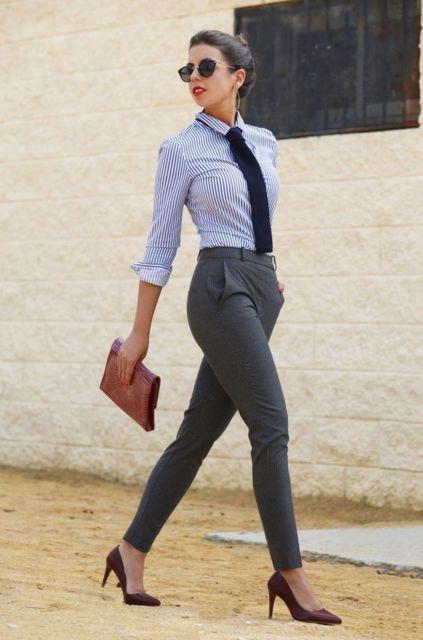 Mulher vestindo calça social, camisa azul e lenço imitando gravata.