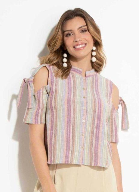 modelo usa camisa social feminina e blusa de manguinha curta.