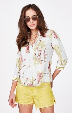 Modelo usa camisa social estampada branca com saia amarela.