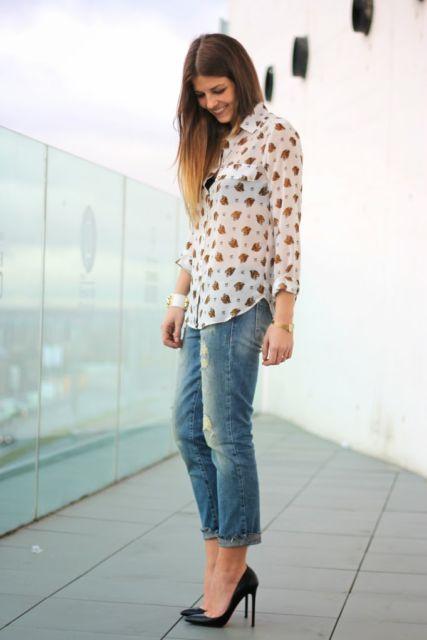 modelo usa calça jeans e camisa estampada transparente com saspto preto.