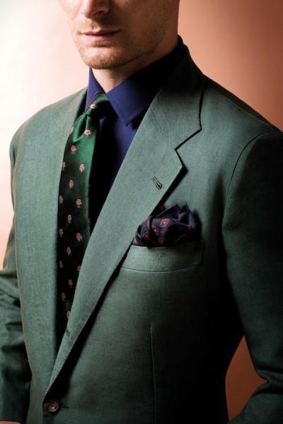 Um lindo terno verde escuro com gravata estampada e um lenço escuro