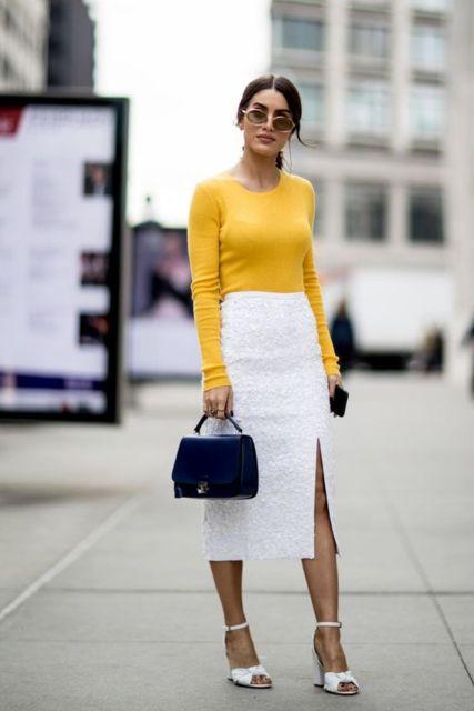 Mulher com saia lápis branca e blusa mostarda.