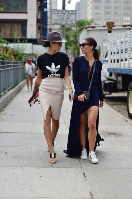 Foto com duas mulheres, uma usando vestido e a outra com saia lápis com fenda e t-shirt preta.