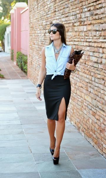 Mulher com saia lápis de fenda e blusa azul jeans.