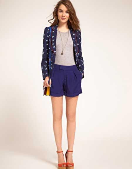 modelo usa short azul, blusa, casaquinho e sapato.