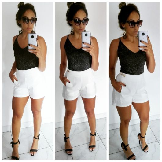 modelo usa short branco, sandália e blusa preta.