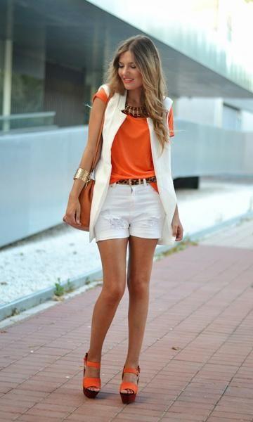 modelo usashort branco, camiseta laranja, colete branco e sapato laranja.
