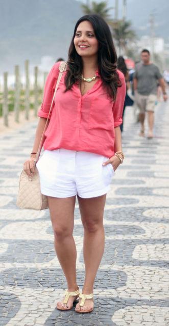 modelo veste camisa rosa, short branco e sandali rasteira.