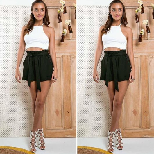 modelo veste short preto, cropped branco e sandália de amarraçao.
