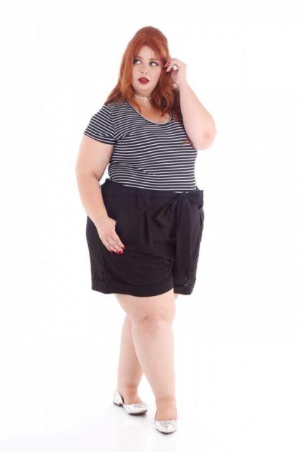 modelo usa short preto com blusa branca de listras horizontais.