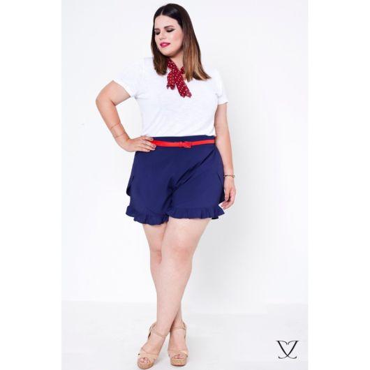 modelo usa short azul, blusa branca e sapato nude.