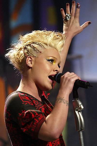 Pink também aparece com tattoos de frases nos braços