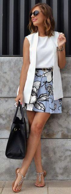 Look com saia com estampa floral e colete branco.