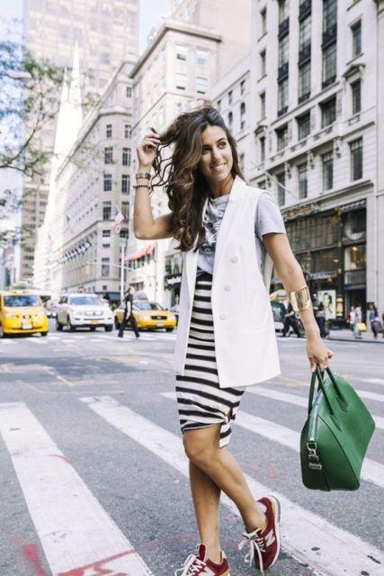 Mulher com saia listrada, bolsa verde e colete branco.