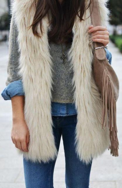 Look com calça e camisa jeans, blusa cinza e colete branco de pelo.