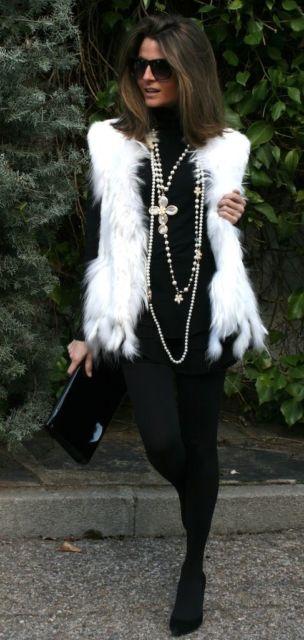 Mulher com calça e blusa preta e colete branco de pelo.