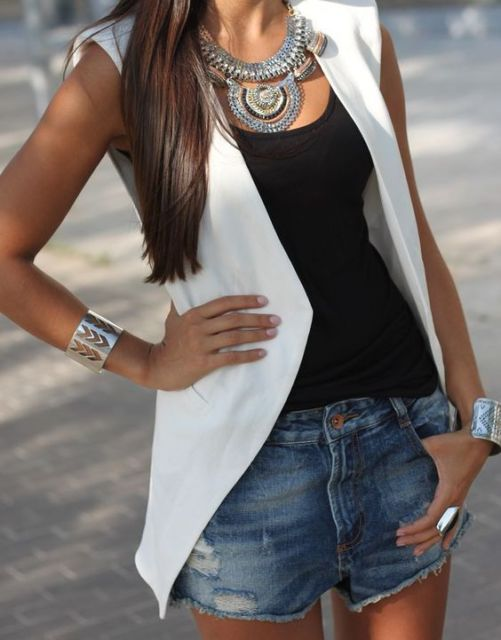 Mulher usando shorts jeans, regata preta e colete branco.