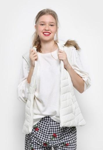 Modelo com calça xadrez, camiseta branca e colete.