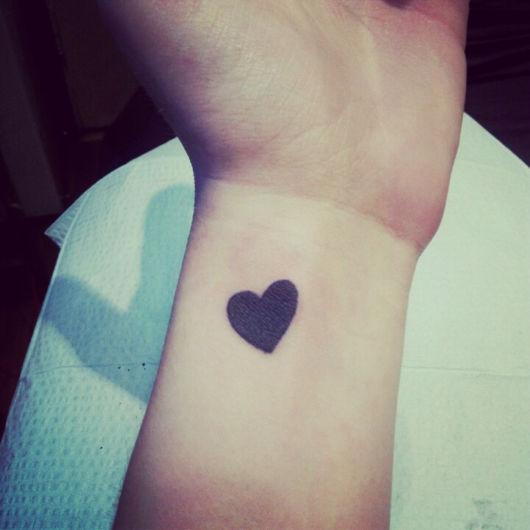 taugaem de coração no pulso pintado de preto.