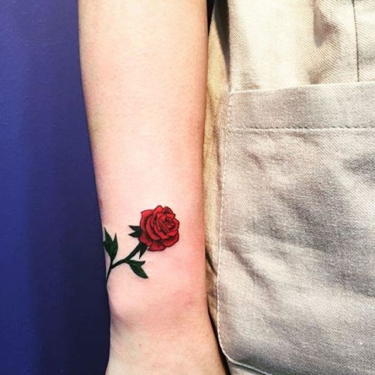tatuagem de rosa vermelha e verde no punho.