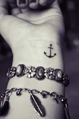 tatuagem de âncora no canto do pulso.
