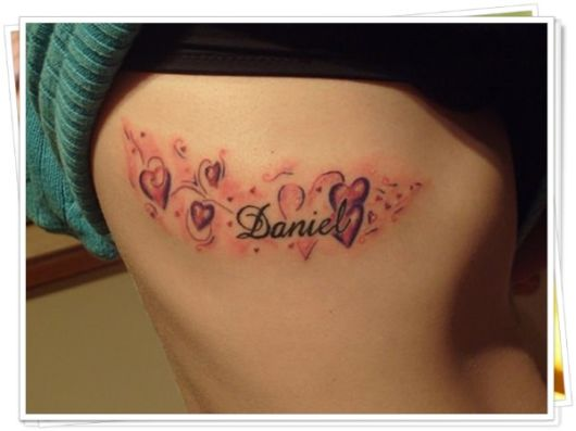 Tatuagem grande na costela com muitos corações e sombreado colorido