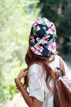 Mulher com camiseta branca, mochila e boné florido.