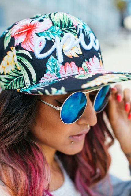Mulher com mechas rosas no cabelo, óculos espelhado e boné florido.