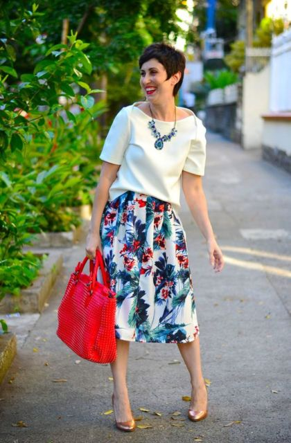 Mulher com saia estampada e blusa branca.